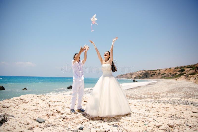 Szczęśliwy uśmiechnięty państwo młodzi wręcza uwalniać białe gołąbki na słonecznym dniu dryftowego morza Śródziemnego połowów tuń obraz stock