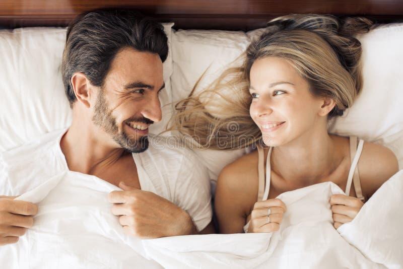 Szczęśliwy uśmiechnięty pary lying on the beach na łóżku w sypialni zdjęcie stock