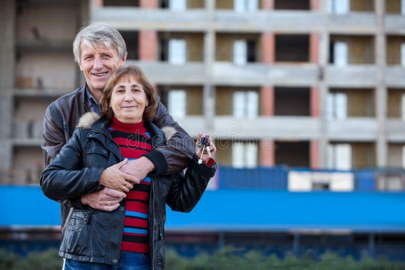 Szczęśliwy uśmiechnięty pary obejmować plenerowy z domu kluczem w ręce, copyspace obraz stock