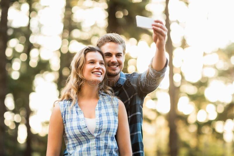 Szczęśliwy uśmiechnięty pary obejmowanie i brać selfies zdjęcie stock