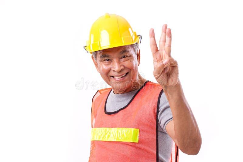 Szczęśliwy, uśmiechnięty pracownik budowlany wskazuje w górę 3 palców, gestykuluje obraz stock