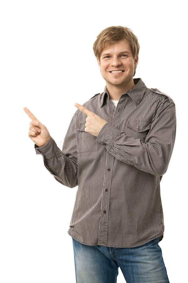 Szczęśliwy uśmiechnięty przypadkowy mężczyzna wskazuje wycinankę zdjęcie royalty free