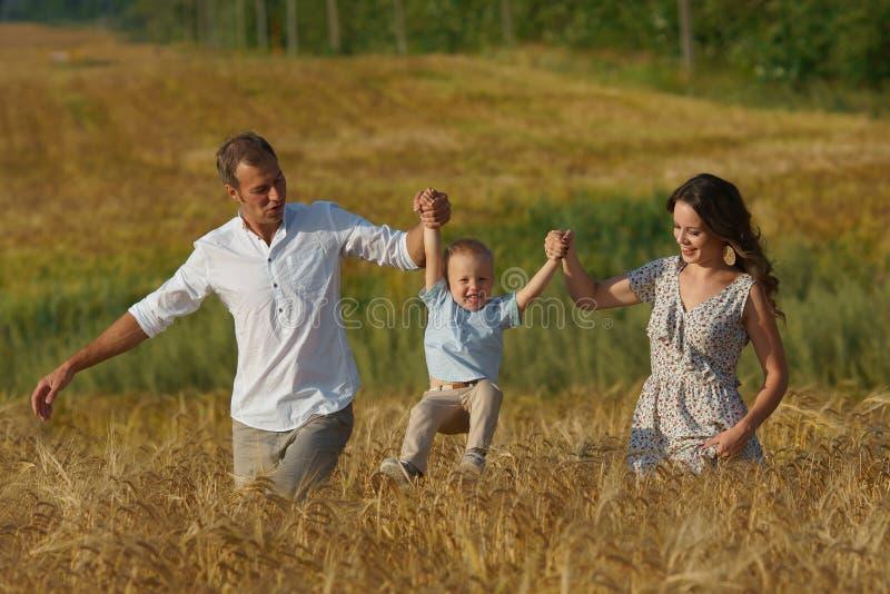 Szczęśliwy uśmiechnięty rodzinny odprowadzenie przez pszenicznego pola zdjęcia stock