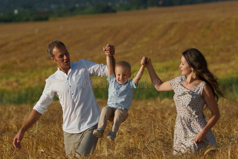Szczęśliwy uśmiechnięty rodzinny odprowadzenie przez pszenicznego pola obraz stock