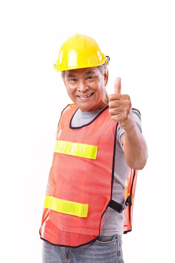 Szczęśliwy, uśmiechnięty starszy pracownik budowlany daje kciukowi up, obraz stock