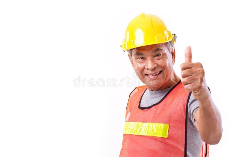 Szczęśliwy, uśmiechnięty starszy pracownik budowlany daje kciukowi up, fotografia royalty free