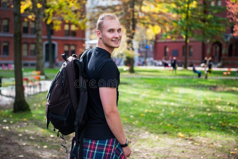 Szczęśliwy uśmiechnięty studencki mężczyzna z plecakiem iść studiować w kampusie zdjęcia stock
