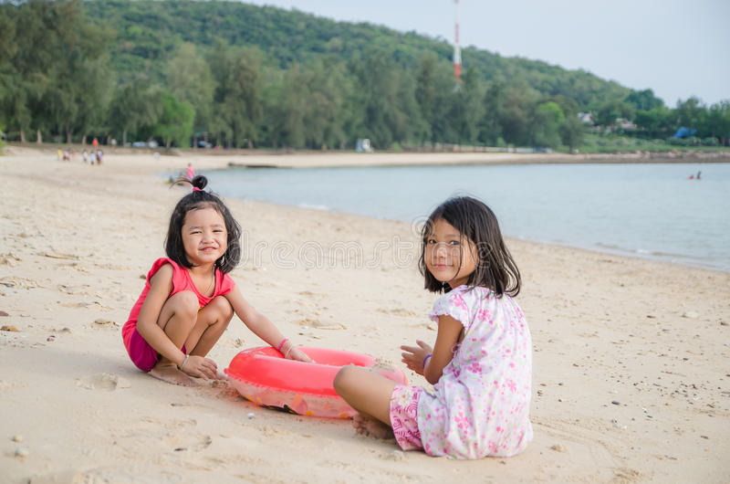 Szczęśliwy uśmiechu azjata żartuje dziewczyny - Tajlandzki dziecko bawić się piasek na bea fotografia royalty free