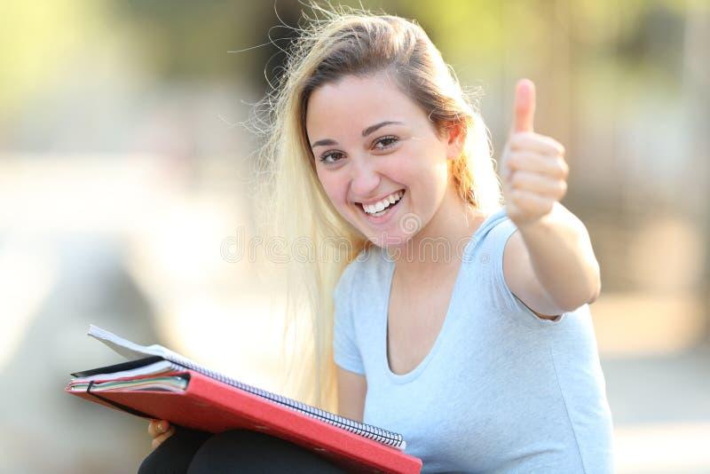 Szczęśliwy uczeń z aprobat spojrzeniami przy kamerą fotografia stock