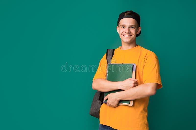Szczęśliwy uczeń z książkami i plecakiem nad tłem obrazy royalty free