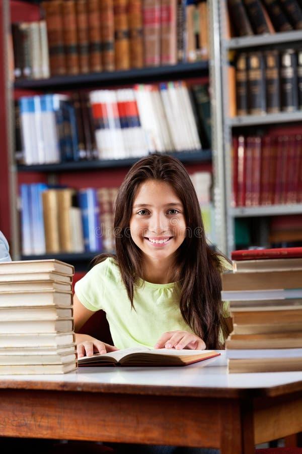Szczęśliwy uczennicy obsiadanie Z stertą Wewnątrz książki fotografia stock