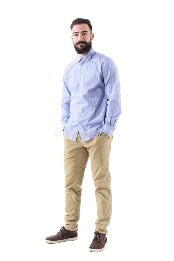 Szczęśliwy ufny brodaty biznesowy mężczyzna patrzeje kamerę w formalnej odzieży z rękami w kieszeniach zdjęcia stock