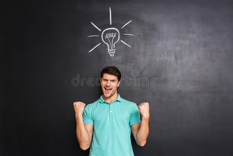 Szczęśliwy ufny młody człowiek odświętności sukces i mieć pomysł fotografia stock