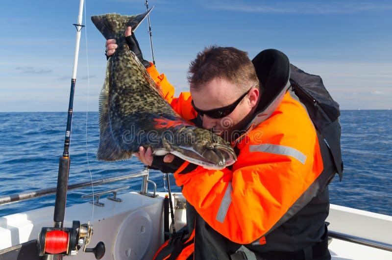 Szczęśliwy wędkarz daje buziakowi halibuta połowu trofeum obraz stock