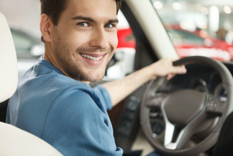 Szczęśliwy właściciel samochodu przy przedstawicielstwem handlowym. Przystojni młodzi człowiecy siedzi przy zdjęcia royalty free