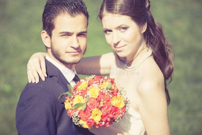 Szczęśliwy właśnie zamężny państwo młodzi na zielonej trawy tle zdjęcie stock