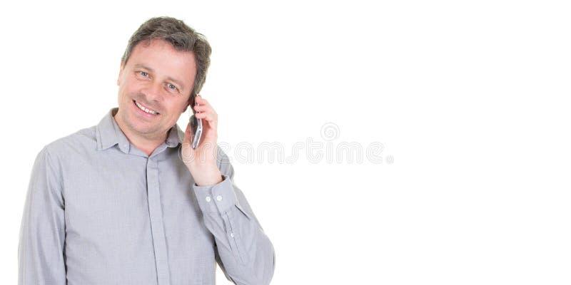 Szczęśliwy w średnim wieku biznesmen opowiada na telefonie komórkowym w białej szablon sieci tła kopii przestrzeni obraz stock