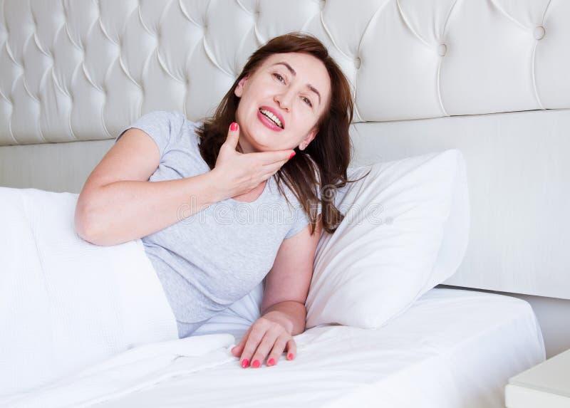 Szczęśliwy w średnim wieku kobiety kłamstwo w łóżku Dzień dobry i sen pojęcie Przekwitanie i zdrowy styl życia Selekcyjna ostrość zdjęcia royalty free