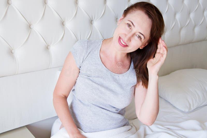 Szczęśliwy w średnim wieku kobiety kłamstwo w łóżku Dzień dobry i sen pojęcie Przekwitanie i zdrowy styl życia Selekcyjna ostrość fotografia royalty free