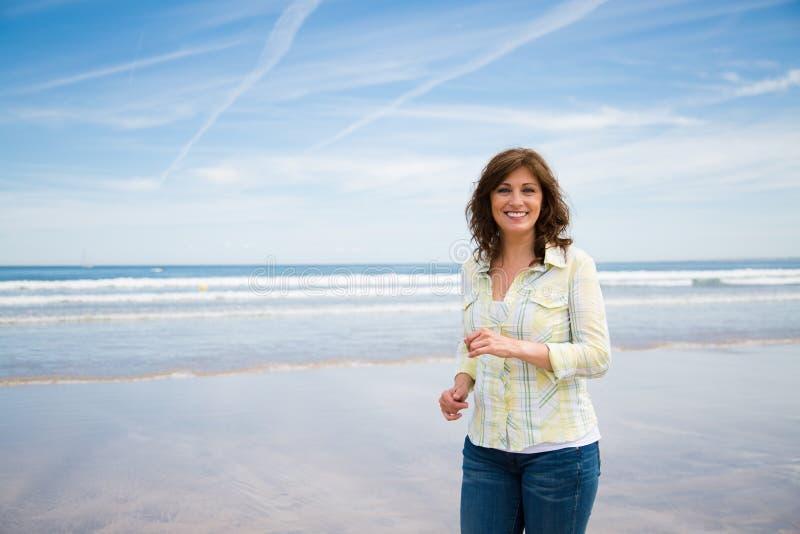 Szczęśliwy w średnim wieku kobiety odprowadzenie na plaży fotografia stock