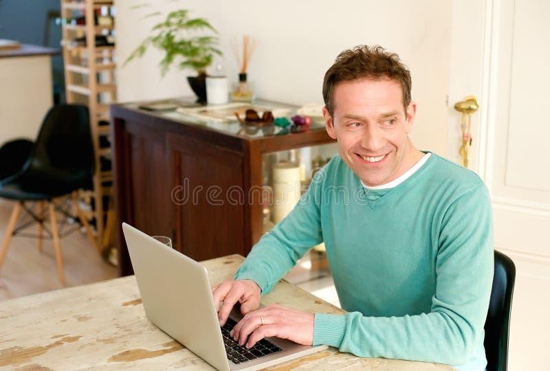 Szczęśliwy w średnim wieku mężczyzna używa laptop w domu obraz royalty free