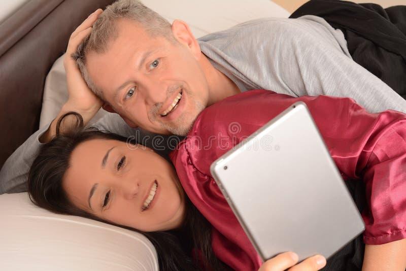 Szczęśliwy w średnim wieku pary dopatrywania wideo na pastylce w domu fotografia royalty free