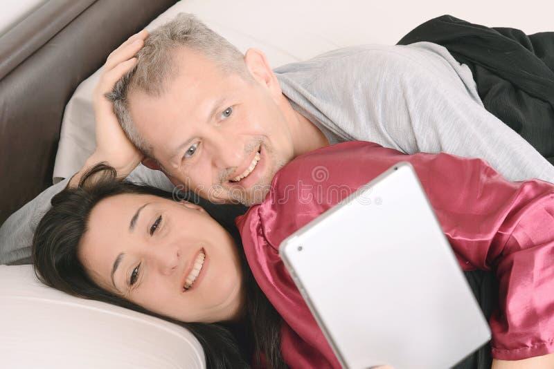 Szczęśliwy w średnim wieku pary dopatrywania wideo na pastylce w domu zdjęcie royalty free