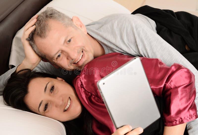 Szczęśliwy w średnim wieku pary dopatrywania wideo na pastylce w domu zdjęcie stock