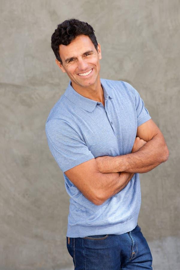 Szczęśliwy wieka średniego mężczyzna ono uśmiecha się z rękami krzyżować fotografia stock