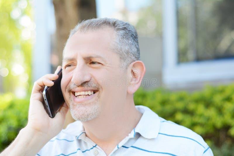 Szczęśliwy wieka średniego mężczyzna opowiada na telefonie zdjęcia royalty free