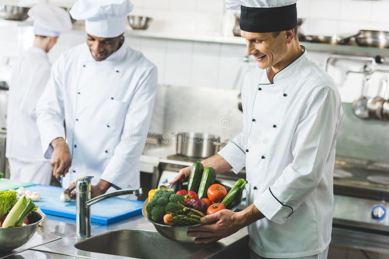 szczęśliwy wielokulturowy szefów kuchni pracować zdjęcie stock
