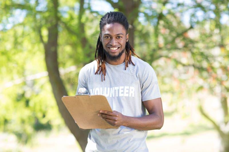 Szczęśliwy wolontariusz w parkowym mienie schowku fotografia stock