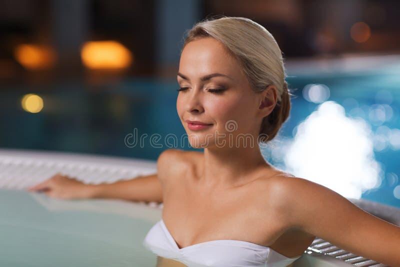 Szczęśliwy womani obsiadanie w jacuzzi przy poolside obrazy royalty free