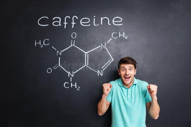 Szczęśliwy z podnieceniem mężczyzna odświętności sukces nad patroszoną kofeiny molekuły strukturą fotografia royalty free