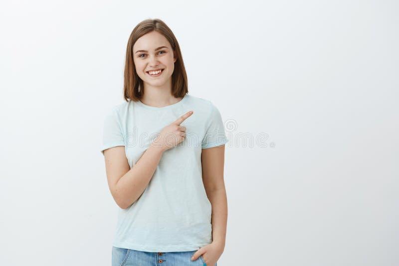 Szczęśliwy zadowolony i beztroski młody żeński uczeń stosuje dobra uniwersytecka promuje kopii przestrzeń nad popielatą ścianą zdjęcie royalty free
