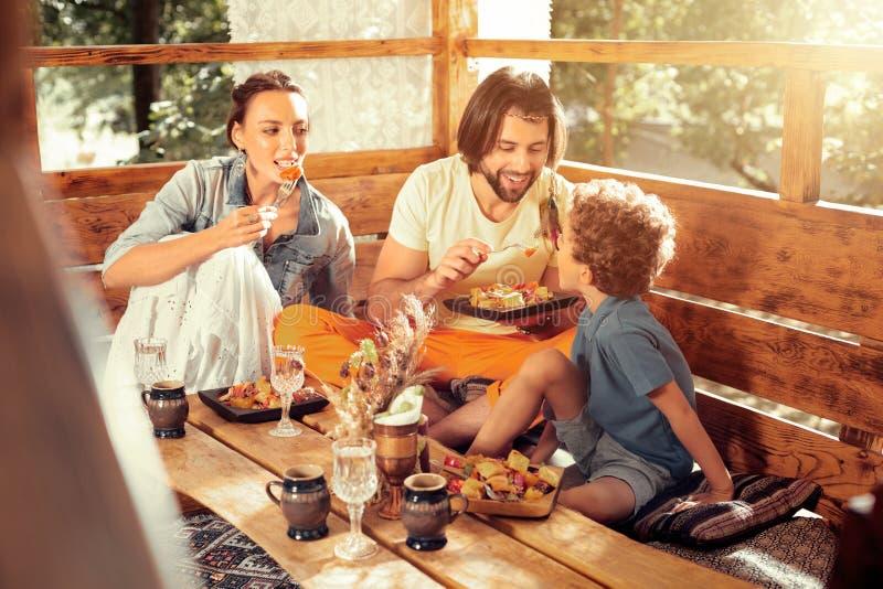 Szczęśliwy zadowolony mężczyzna karmi jego syna z sałatką obrazy stock