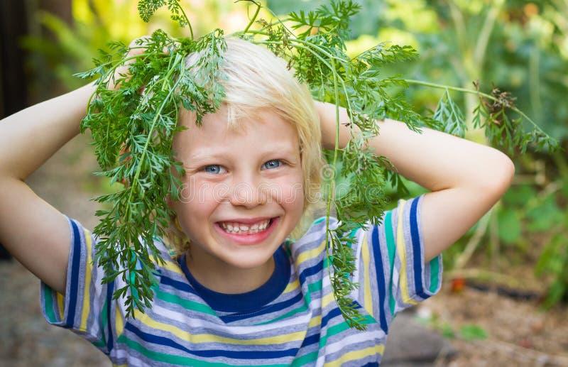 Szczęśliwy zdrowy dziecko z marchewka wierzchołkiem w jarzynowym ogródzie zdjęcia royalty free
