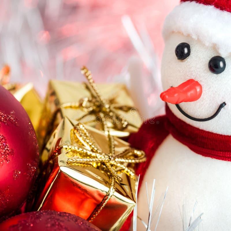Szczęśliwych Świąt Bożego Narodzenia, nowy rok, bałwan, prezenty w złocistych pudełkach i czerwone piłki na różowym bokeh tle, zdjęcie royalty free