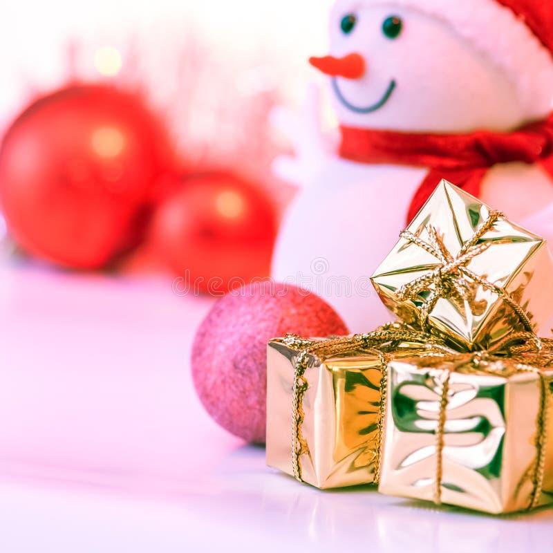 Szczęśliwych Świąt Bożego Narodzenia, nowy rok, bałwan, prezenty w złocistych pudełkach i czerwone piłki na różowym tle, zdjęcie stock