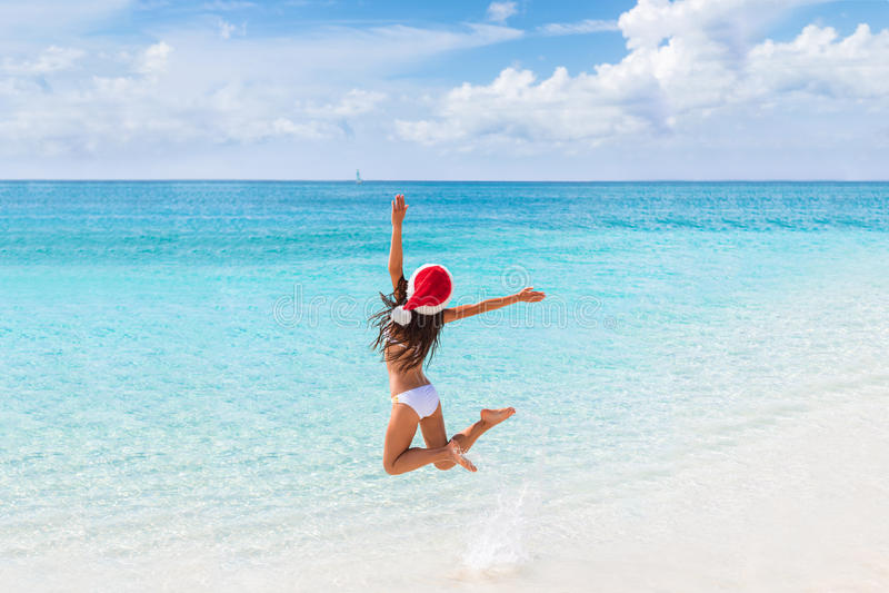 Szczęśliwych bożych narodzeń dziewczyny kapeluszowy doskakiwanie radość na plaży obrazy royalty free