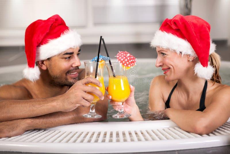 Szczęśliwych bożych narodzeń Santa para w gorącej balii wakacje zdjęcia royalty free