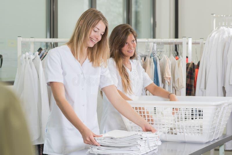 Szczęśliwych młodych kobiet pralniani pracownicy przy suchymi czyścicielami zdjęcie royalty free