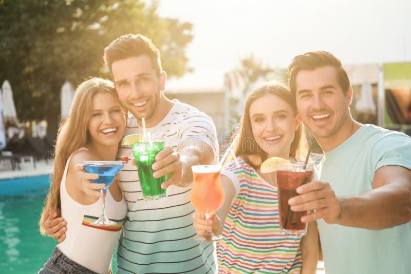 Szczęśliwych młodych przyjaciół, świeżych letnich koktajli relaksujących się w pobliżu basenu fotografia stock