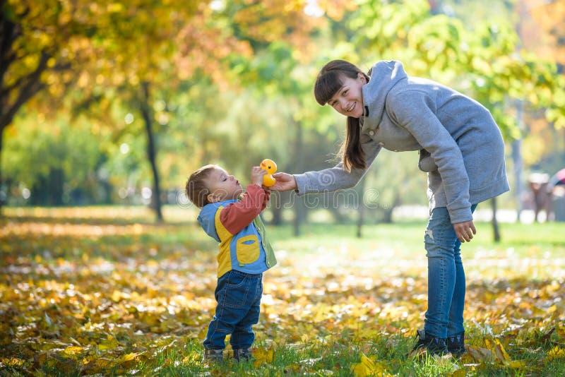 Szczęśliwych potomstw macierzysty bawić się z dzieckiem w jesień parku z żółtymi liśćmi klonowymi Rodzinny odprowadzenie outdoors fotografia royalty free