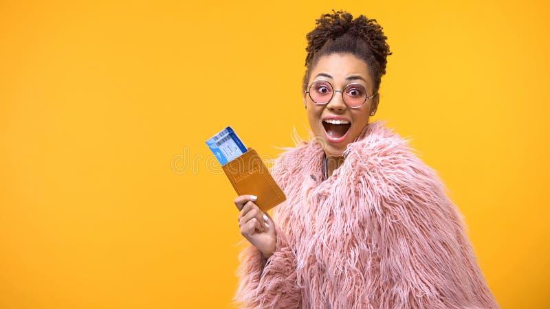 Szcz??liwa amerykanin kobieta pokazuje paszport z biletami, urlopowa wycieczka turysyczna, tania obraz royalty free