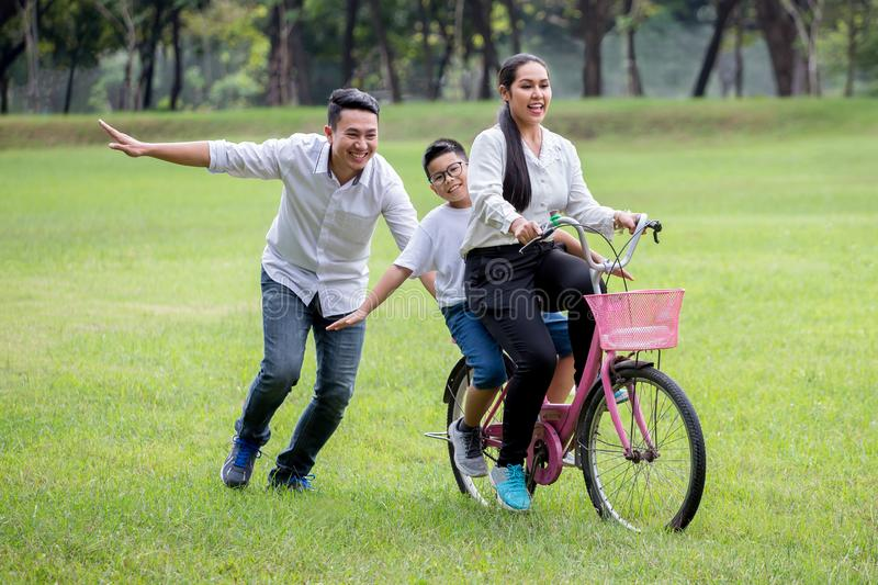 szcz??liwa azjatykcia rodzina, rodzice i ich dzieci jedzie rower w parku wp?lnie, ojc?w pchni?cia matka i syn na bicyklu ma zabaw zdjęcia stock