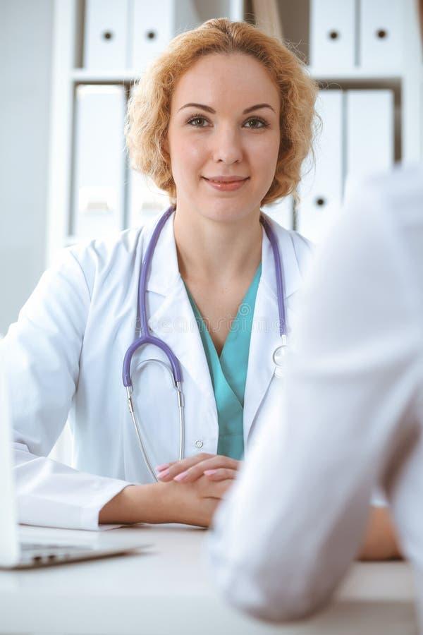 Szcz??liwa blondynki kobiety lekarka i pacjent dyskutuje badanie medyczne rezultaty Medycyny, opieki zdrowotnej i pomocy poj?cie, fotografia stock