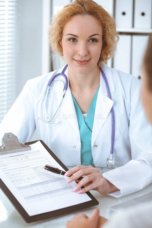 Szcz??liwa blondynki kobiety lekarka i pacjent dyskutuje badanie medyczne rezultaty Medycyny, opieki zdrowotnej i pomocy poj?cie, zdjęcie stock