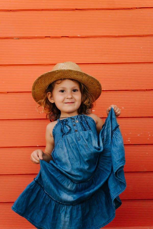 Szcz??liwa dziecko dziewczyna w lato kapeluszu i pi?knej b??kit sukni przeciw pomara?cze ?cianie zdjęcia royalty free