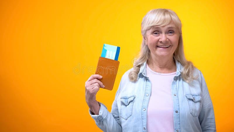 Szcz??liwa emeryt dama pokazuje paszport i bilety, agencji podr??y reklama obrazy stock